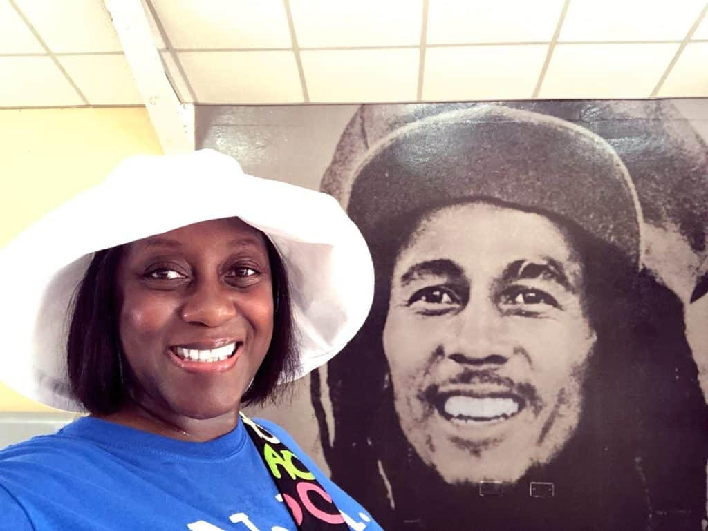 Ola in front of a mural of Bob Marley