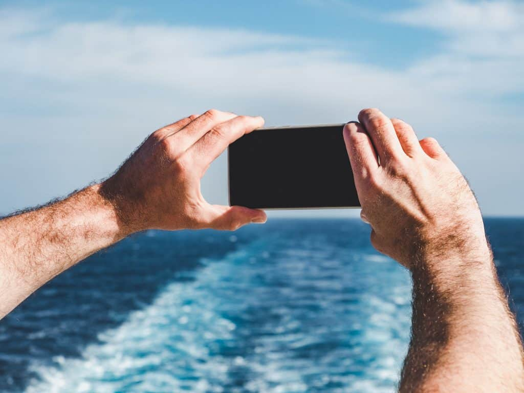 Fashionable man holding a mobile phone on the empty deck of a cruise liner against the backdrop of the sea waves.