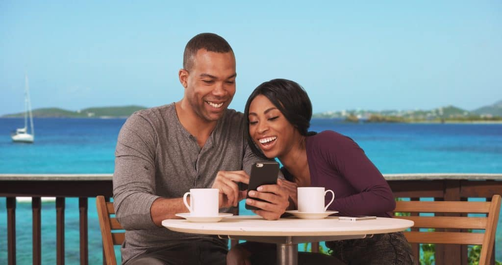 Cruise Line Apps: Couple on honeymoon sitting at restaurant with ocean view drinking coffee